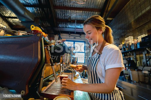 Happy barista making coffee at a cafe on the bar counter and smiling - food service occupation concepts