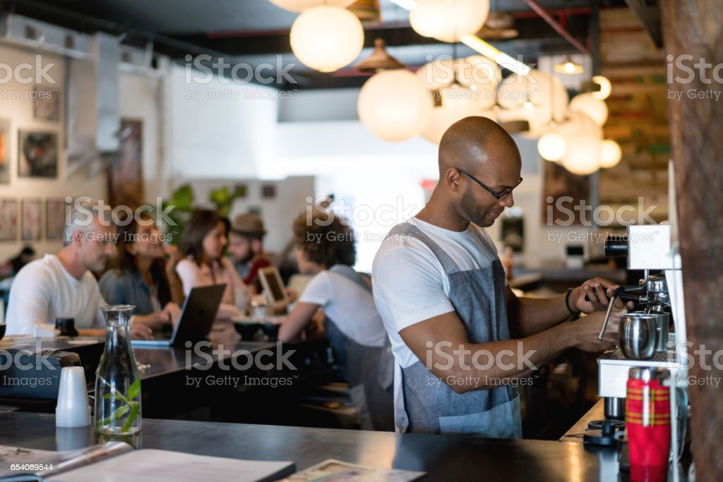 Barista making coffee at a cafe stock photo