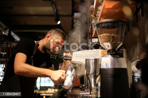 Barista Making Coffee For Customers At Cafe