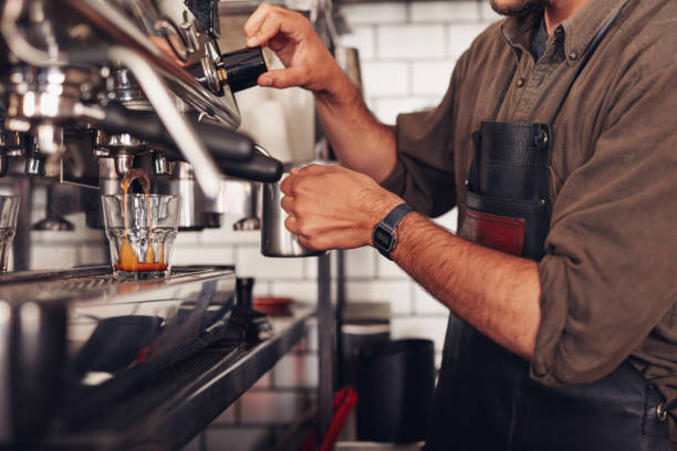 barista making coffee using a coffee maker - barista stock photos and pictures