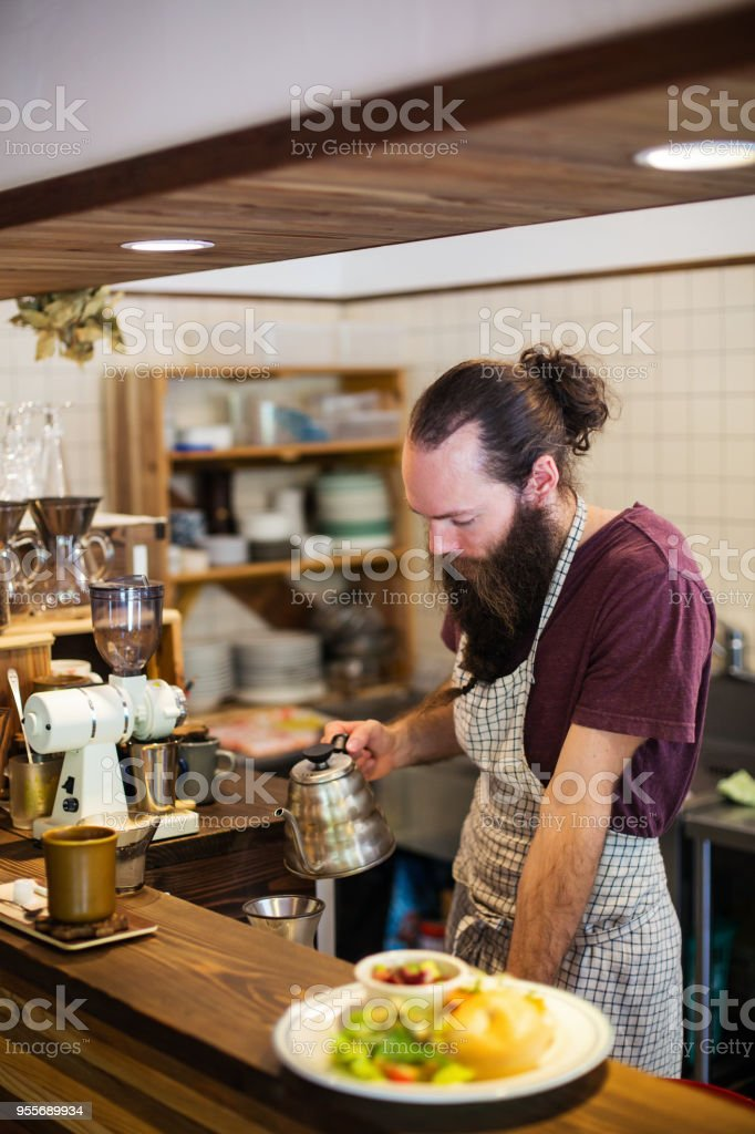 Barista making coffee with a meal ready for serving on the counter stock photo