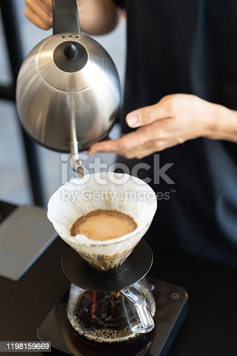 Barista making drip coffee by pouring hot water from goose neck kettle to filter cone.