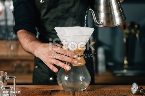 Barista pouring hot water from kettle into white filter for drip coffee. Barista working in coffee shop, wearing dark uniform.