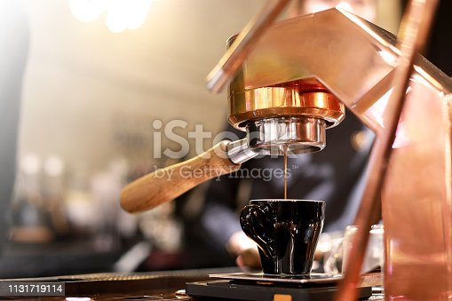 istock Barista making hot espresso coffee with the coffee machine in the coffee shop or cafe, Foods and drink concept. Warm Tone. 1131719114