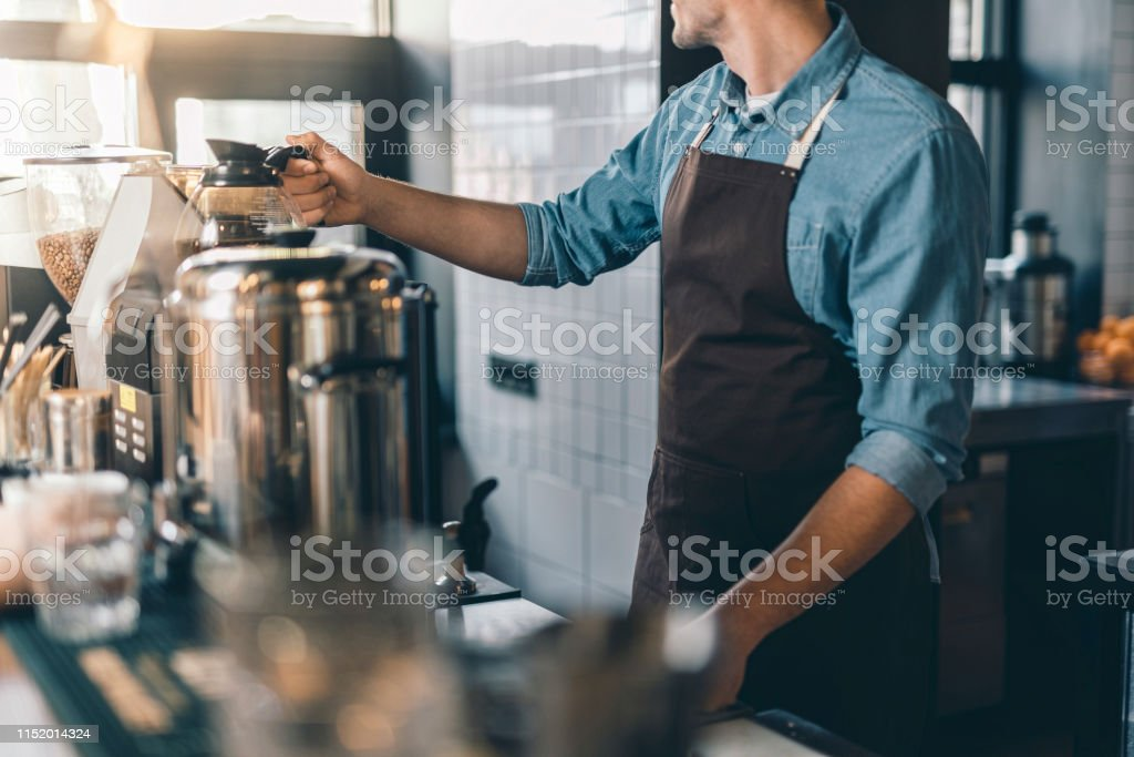 Close up of a man at the bar counter turning his head while putting a...