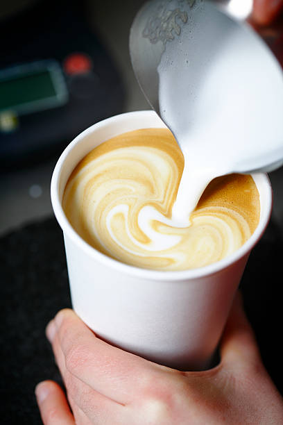 Barista pouring a cafe latte espresso to go