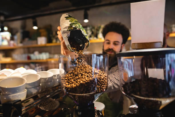 Barista gießt Kaffeebohnen in Kaffeemaschine – Foto