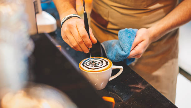 barista pouring latte art with chocolate sauce - barista making coffee stock pictures, royalty-free photos & images