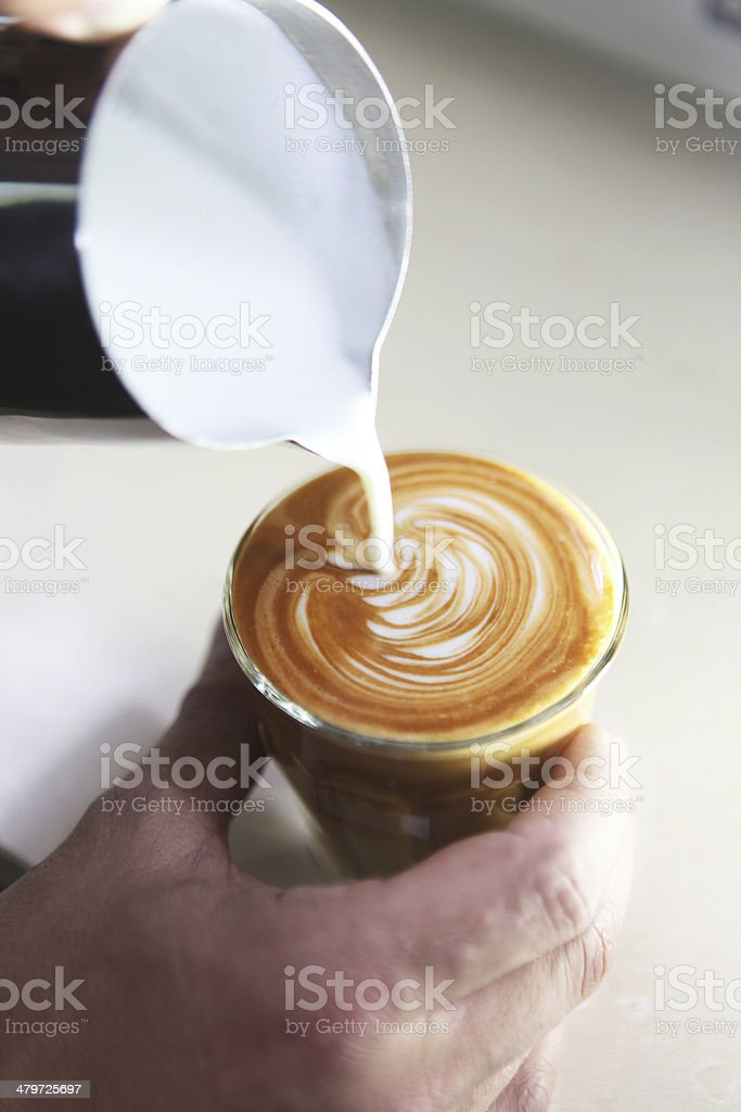barista pouring milk in coffee, close-up stock photo