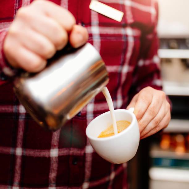 barista gießt milch in kaffeemaschine latte - italienische küchen dekor stock-fotos und bilder
