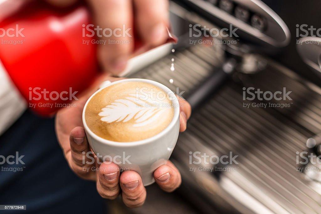 Barista pouring milk stock photo
