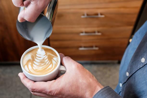 Barista strömenden geschäumter Milch in die Kaffeetasse Latte Kunst zu machen – Foto