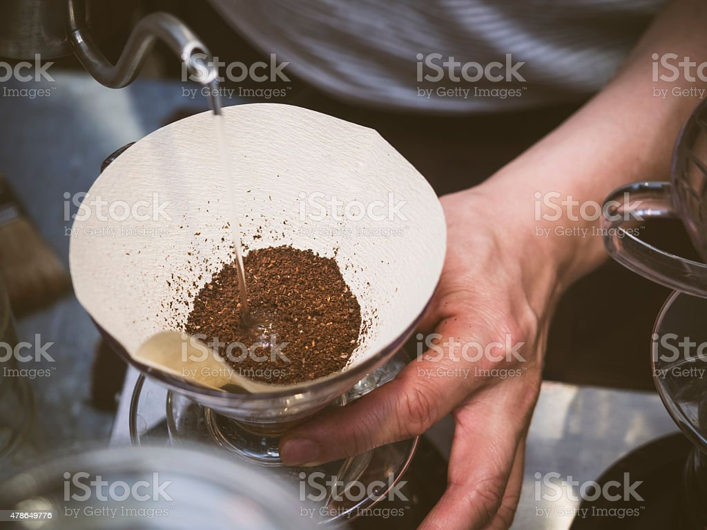 Barista pouring water on coffee ground, Hand drip making coffee stock photo
