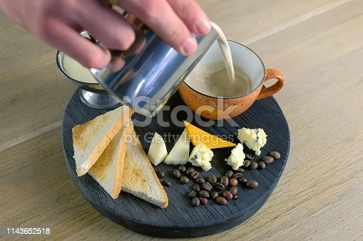 Barista pours fresh cheese coffee from pitcher to cup on tray with melted cheese and bread. Hands close-up