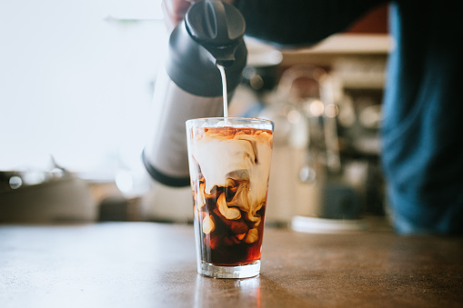 A man pours cold whole milk in to a glass of iced coffee in a cafe.  A cool refreshing drink for a hot summer day.