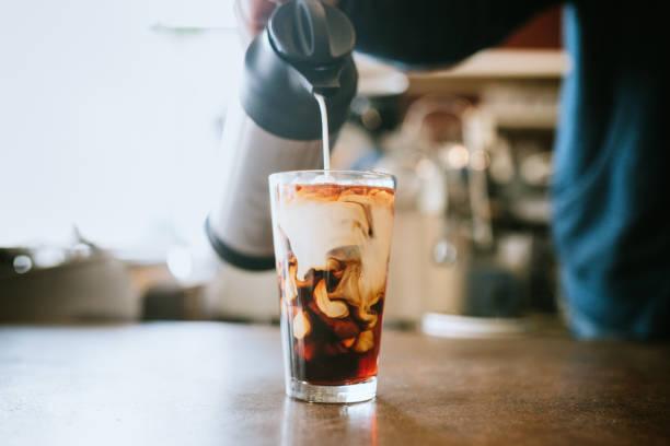 Barista pours Milch in kalten Brew Kaffee – Foto