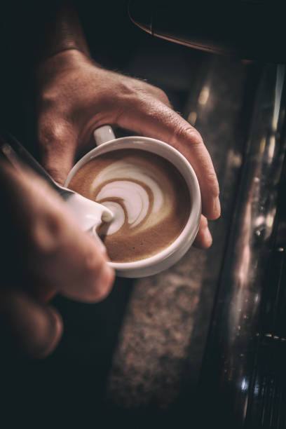 barista pours milk - barista making coffee stock photos and pictures