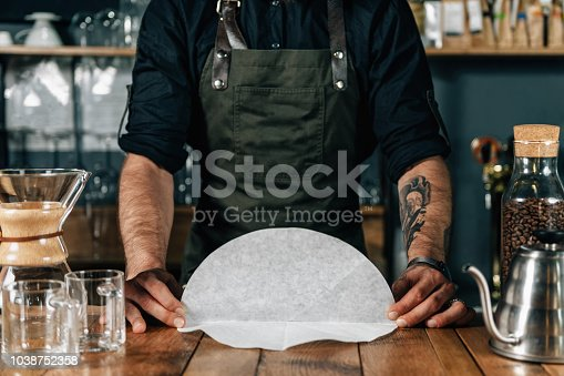 Barista preparing filter for drip coffee. Young bearded barista working in coffee shop. Tattooed arms, wearing dark uniform.
