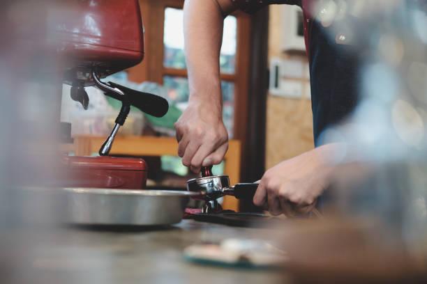 Barista Kaffee in der Maschine-Halterung drücken. – Foto