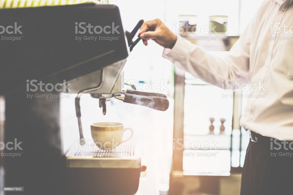Barista releasing stream by cofee machine with cup for prepares espresso coffee in his coffee shop. stock photo