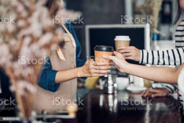 Barista served take away hot coffee cup to customer at counter bar in picture id968993540?b=1&k=6&m=968993540&s=612x612&h=ljscpblectcazgxcac9bz kdli9mg 1b5j2btwzoxho=