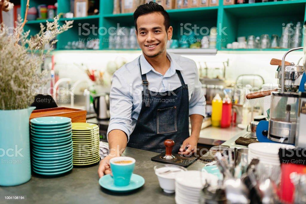 Barista Serving Cappuccino in Coffee Shop stock photo