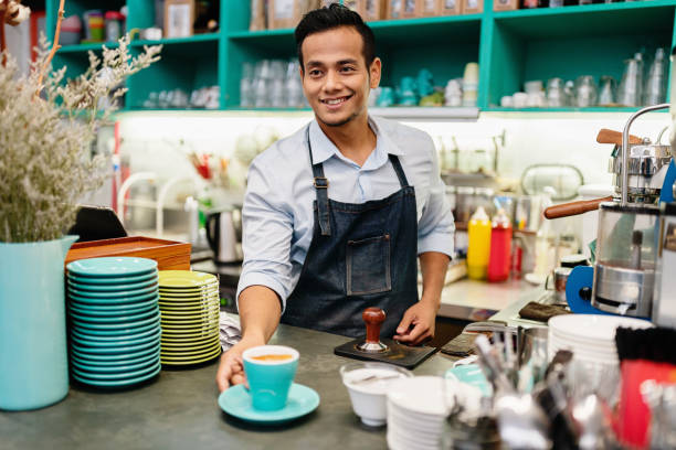 Barista Serving Cappuccino in Coffee Shop stock photo