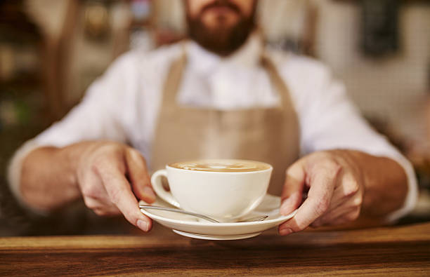 barista serving cup of fresh coffee for you - barista stock photos and pictures