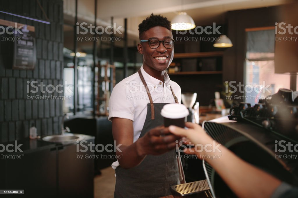 Barista serving customers inside a coffee shop stock photo