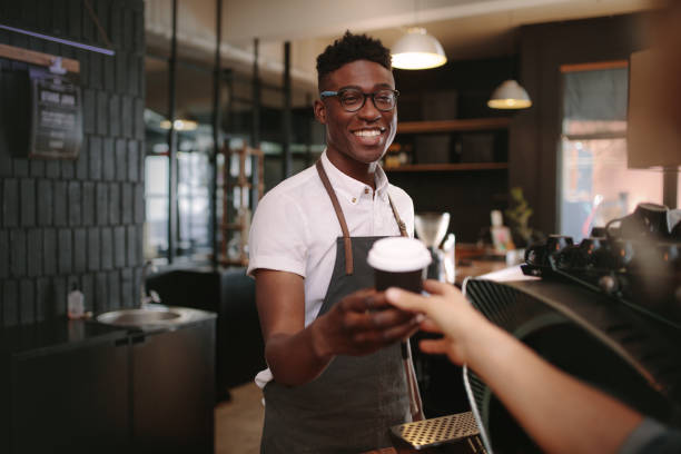 barista serving customers inside a coffee shop - barista stock photos and pictures