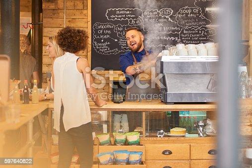 istock Barista sharing a joke with customer 597640822