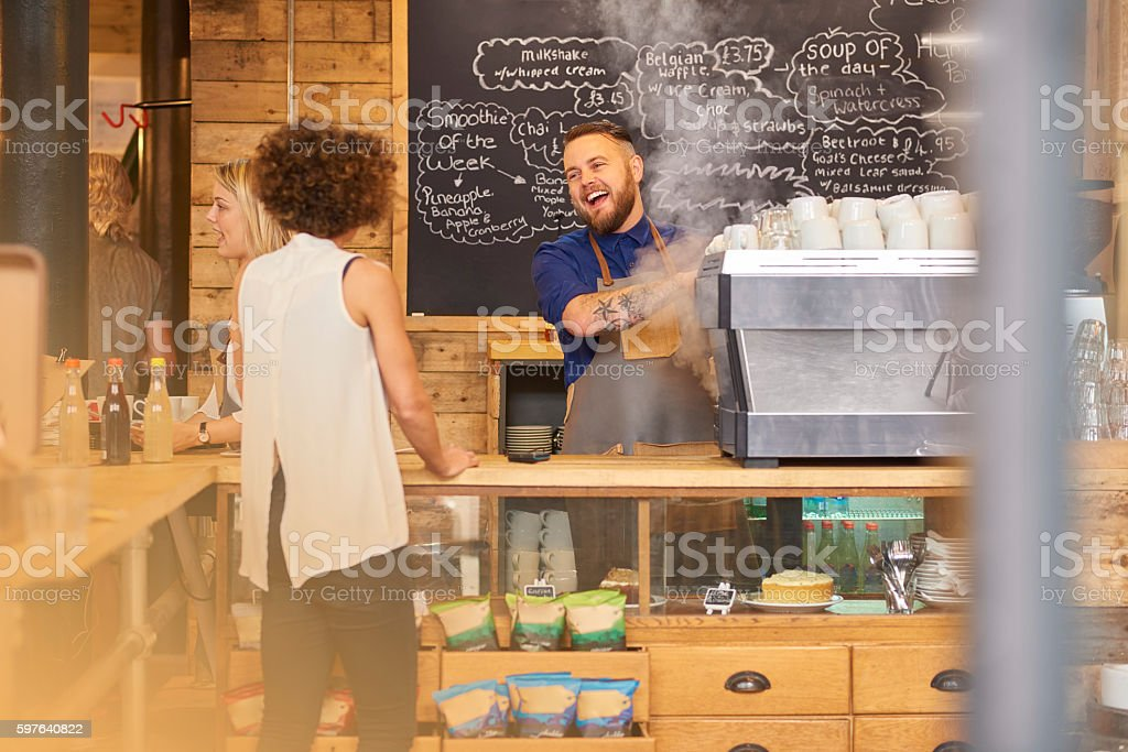 Barista sharing a joke with customer stock photo