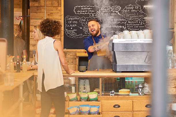 barista sharing a joke with customer - barista stock photos and pictures