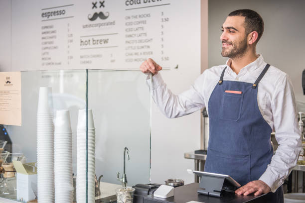 Barista Standing at the Cash Register of a Local Coffee Shop Male entrepreneur standing proud next to the tablet register at his neighborhood coffee shop. armenian ethnicity stock pictures, royalty-free photos & images