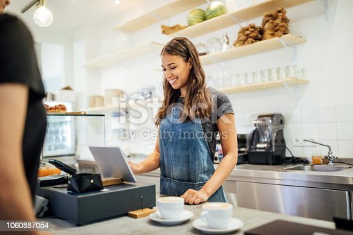 Female barista standing at cafe counter entering customer order on digital tablet. Cafe owner taking order from customer at coffee shop counter.