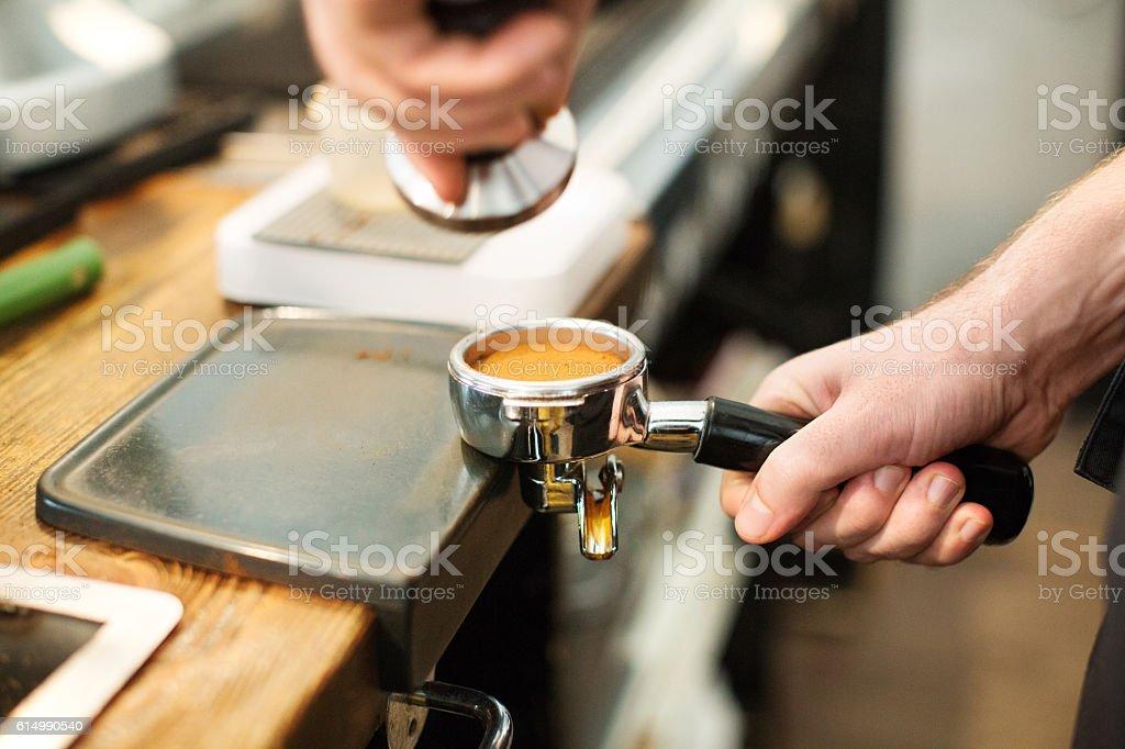 Barista tamping fresh ground coffee stock photo