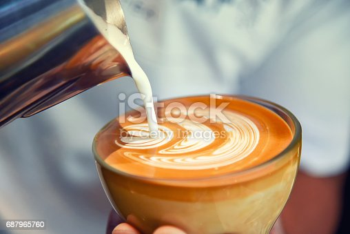 istock Barista using coffee machine preparing fresh coffee or latte art and pouring into cup at coffee shop and restaurant 687965760