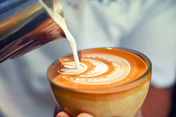 barista using coffee machine preparing fresh coffee or latte art and pouring into cup at coffee shop and restaurant - barista making coffee stock pictures, royalty-free photos & images
