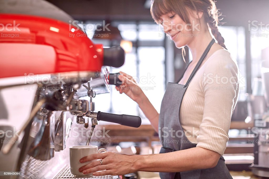 Barista using espresso machine in coffee shop stock photo