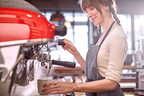 barista using espresso machine in coffee shop - barista stock photos and pictures