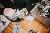 A woman works in her small modern coffee shop, enjoying the perfection of her craft coffee beverage preparation. She pours froth art for a customers Matcha green tea latte.