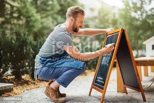 istock Barista writing today's special on the chalkboard 1060886434