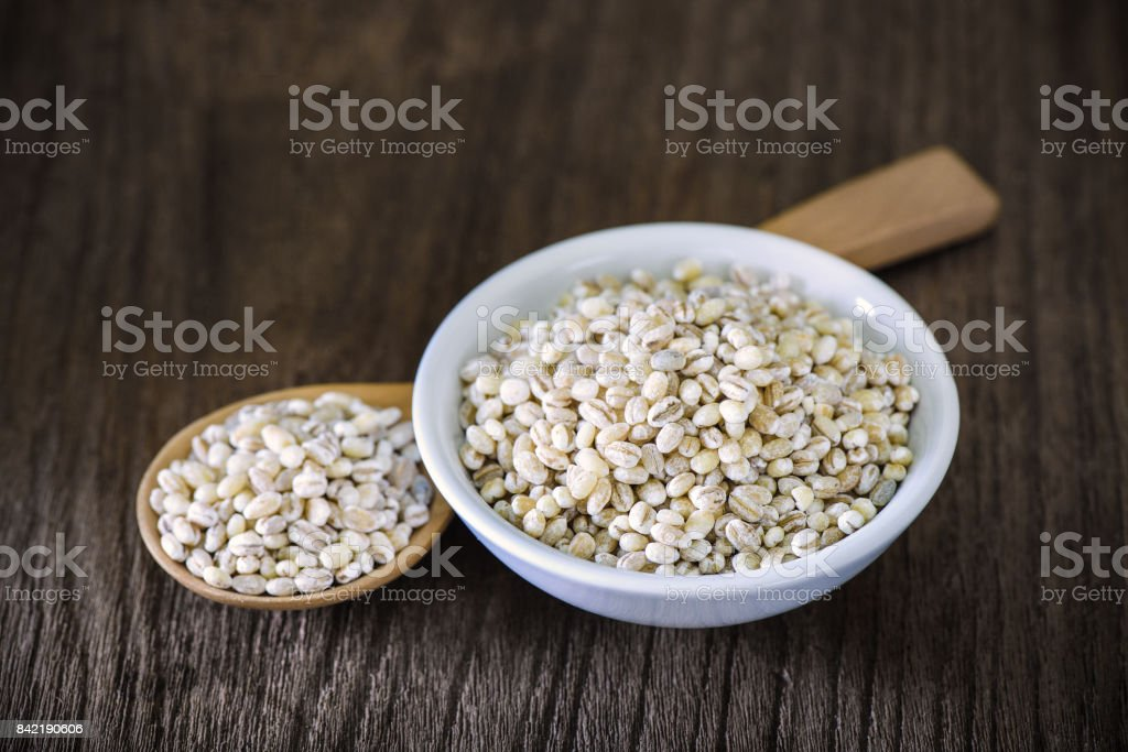 Barley in wood Spoon and bowl stock photo