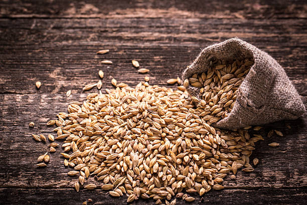 barley on wooden table - barley stock pictures, royalty-free photos & images