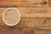 Top view of white bowl full of barley over wooden table