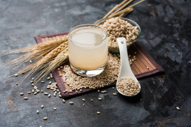 barley water in glass with raw and cooked pearl barley wheat/seeds. selective focus - barley stock pictures, royalty-free photos & images