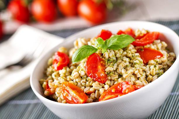 Barley with pesto sauce and tomatoes. Barley with pesto sauce and tomatoes. spelt stock pictures, royalty-free photos & images