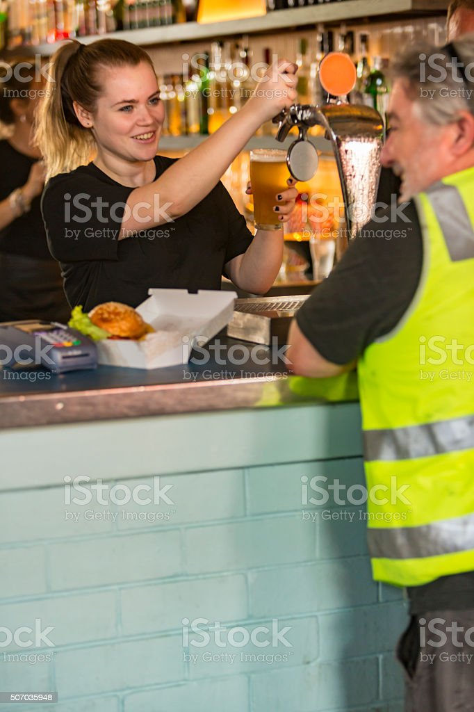 Barmaid Pouring Beer For Workman After Work High Visibility Clothes stock photo