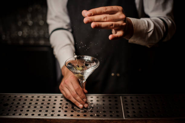 Barman adding salt into a strong martini cocktail Barman adding salt into a strong martini cocktail decorated with a green olive on the bar martini stock pictures, royalty-free photos & images