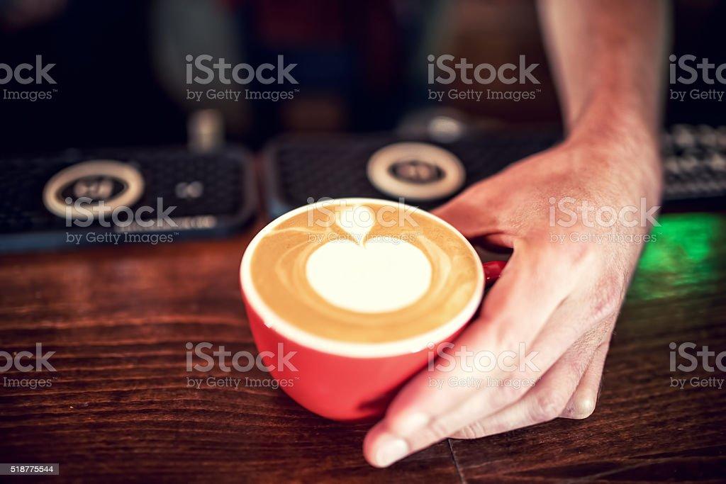 Barman and barista creating latte art with milk foam stock photo